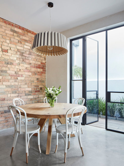 Photo Of A Contemporary Dining Room In Melbourne With Red Walls Concrete Floors And Grey