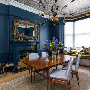 Modelo de comedor vintage, cerrado, con paredes azules, suelo de madera en tonos medios, chimenea tradicional, marco de chimenea de madera y suelo marrón