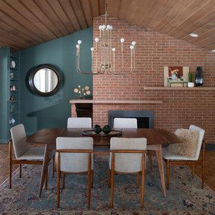 Идея дизайна: большая кухня-столовая в стиле ретро с зелеными стенами, стандартным камином, фасадом камина из кирпича, коричневым полом и паркетным полом среднего тона