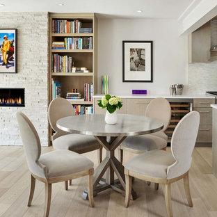 Imagen de comedor de cocina minimalista, pequeño, con paredes grises, suelo de madera clara, suelo beige, chimenea lineal y marco de chimenea de piedra