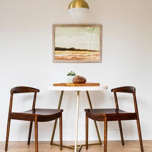 Foto di una piccola sala da pranzo aperta verso la cucina nordica con pareti bianche, pavimento in laminato, nessun camino e pavimento marrone