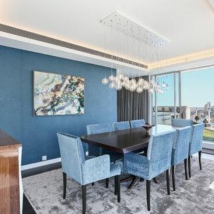 Inspiration pour une salle à manger traditionnelle fermée et de taille moyenne avec un mur bleu, un sol en bois foncé et un sol marron.