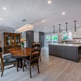 Foto di una grande sala da pranzo aperta verso la cucina moderna con pareti grigie, pavimento in vinile, nessun camino e pavimento grigio