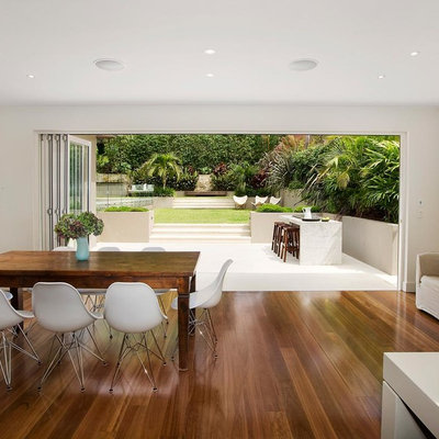 Inspiration for a contemporary medium tone wood floor great room remodel in Sydney with white walls