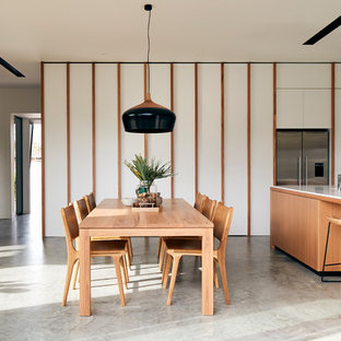 Example of a minimalist concrete floor and gray floor great room design in Melbourne with white walls