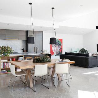 Foto di una sala da pranzo aperta verso il soggiorno contemporanea di medie dimensioni con pareti bianche, pavimento in cemento, camino sospeso e pavimento grigio