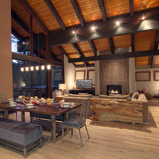Mountain style medium tone wood floor great room photo in Other with beige walls