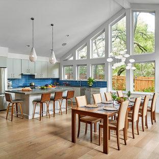 Esempio di una grande sala da pranzo aperta verso la cucina moderna con pareti bianche, parquet chiaro, nessun camino e pavimento beige
