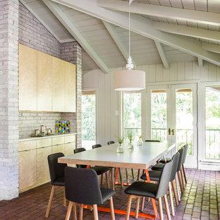 Exemple d'une salle à manger tendance fermée avec un mur blanc et un sol en brique.