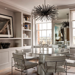 Classic open plan dining room in London with grey walls and medium hardwood flooring.