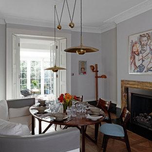 Foto de comedor de cocina vintage, de tamaño medio, con paredes grises, suelo de madera en tonos medios, chimenea tradicional, marco de chimenea de piedra y suelo marrón