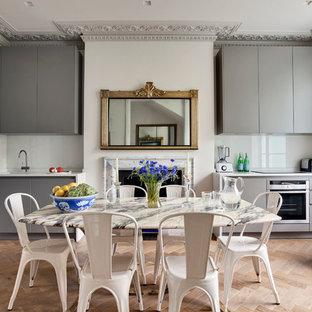 Immagine di una sala da pranzo aperta verso la cucina eclettica di medie dimensioni con pavimento in legno massello medio, pareti grigie, camino classico, cornice del camino in pietra e pavimento marrone