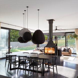 Inspiration för en stor funkis matplats, med vita väggar, betonggolv, svart golv och en öppen vedspis