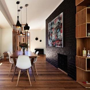 Ejemplo de comedor actual, de tamaño medio, con paredes negras, suelo de madera en tonos medios, chimenea tradicional y marco de chimenea de ladrillo