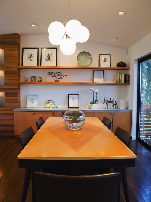 Example Of A Minimalist Dining Room Design In Portland With White Walls And Dark Wood Floors