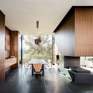 Immagine di una sala da pranzo moderna con pareti marroni, camino bifacciale, cornice del camino in mattoni e pavimento nero