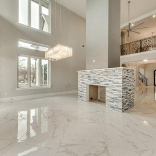 Idee per una grande sala da pranzo aperta verso il soggiorno chic con pareti grigie, pavimento in marmo, camino bifacciale, cornice del camino in pietra e pavimento bianco