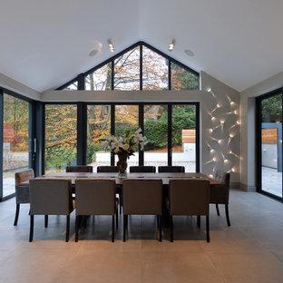 Immagine di una grande sala da pranzo aperta verso la cucina contemporanea con pareti grigie, pavimento con piastrelle in ceramica, nessun camino e pavimento grigio