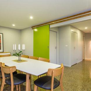 Idee per una sala da pranzo minimal chiusa e di medie dimensioni con pavimento in cemento e pareti grigie