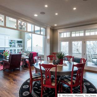 Foto di una grande sala da pranzo aperta verso il soggiorno classica con pareti beige, pavimento in legno massello medio, camino classico, cornice del camino in perlinato e pavimento marrone