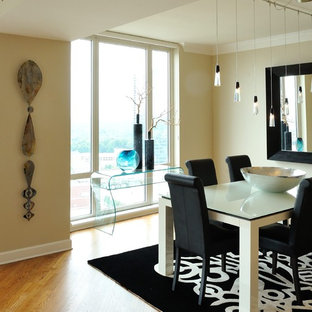 Example of a mid-sized trendy medium tone wood floor enclosed dining room design in Atlanta with beige walls