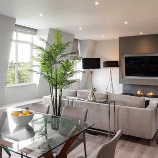 На фото: маленькая столовая в современном стиле с с кухонным уголком, серыми стенами, светлым паркетным полом, стандартным камином, фасадом камина из камня, серым полом и обоями на стенах с