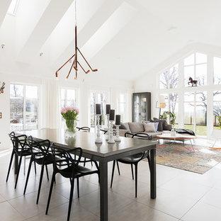 Неиссякаемый источник вдохновения для домашнего уюта: огромная гостиная-столовая в скандинавском стиле с белыми стенами, полом из известняка и бежевым полом без камина