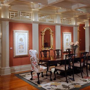Esempio di un'ampia sala da pranzo aperta verso il soggiorno classica con pavimento in legno massello medio e pareti arancioni
