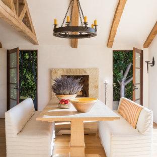 ロサンゼルスの中くらいの地中海スタイルのおしゃれなダイニング (ベージュの壁、淡色無垢フローリング、標準型暖炉、積石の暖炉まわり、ベージュの床、表し梁) の写真