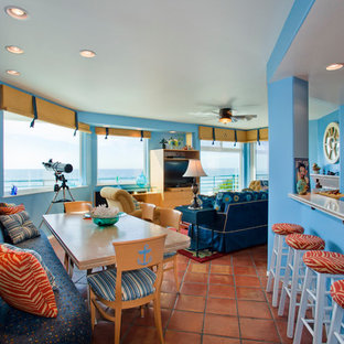 Photo of a small tropical open plan dining in San Diego with blue walls and terra-cotta floors.
