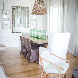 Inspiration for a coastal medium tone wood floor and brown floor dining room remodel in Other with white walls