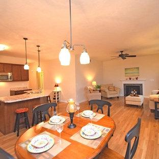 Esempio di una grande sala da pranzo aperta verso la cucina classica con pareti beige, pavimento in legno massello medio, camino classico e cornice del camino in pietra