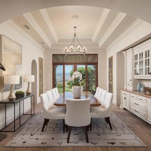 Foto di una sala da pranzo mediterranea con pareti bianche, pavimento in legno massello medio e pavimento marrone