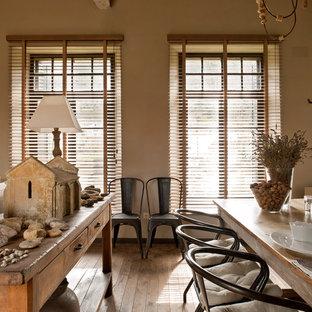 Immagine di una grande sala da pranzo aperta verso il soggiorno country con pareti beige, pavimento in legno massello medio e nessun camino