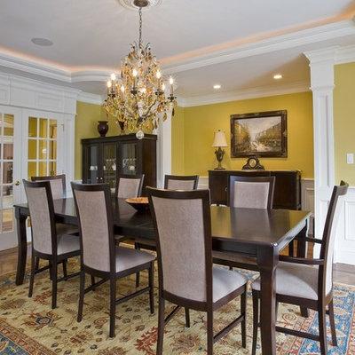 Elegant medium tone wood floor dining room photo in Boston with yellow walls