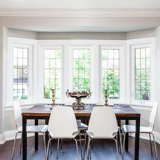Diseño de comedor actual, de tamaño medio, abierto, con paredes grises, suelo de madera oscura, chimenea tradicional, marco de chimenea de madera y suelo marrón