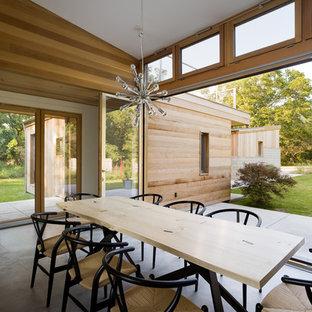 Foto di una grande sala da pranzo aperta verso il soggiorno contemporanea con pavimento in cemento, pareti beige e pavimento grigio