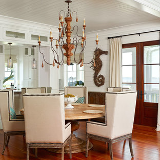 This is an example of a tropical kitchen/dining combo in Charleston with white walls and dark hardwood floors.