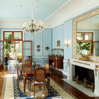 Large elegant medium tone wood floor and brown floor enclosed dining room photo in Boston with blue walls, a stone fireplace and a standard fireplace