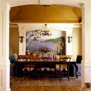 Example of a large ornate medium tone wood floor enclosed dining room design in Denver with yellow walls