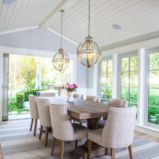 Immagine di una sala da pranzo country chiusa e di medie dimensioni con pareti grigie e parquet chiaro