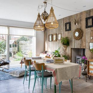 Ispirazione per una sala da pranzo aperta verso il soggiorno eclettica con pareti marroni, parquet chiaro, stufa a legna e cornice del camino in legno