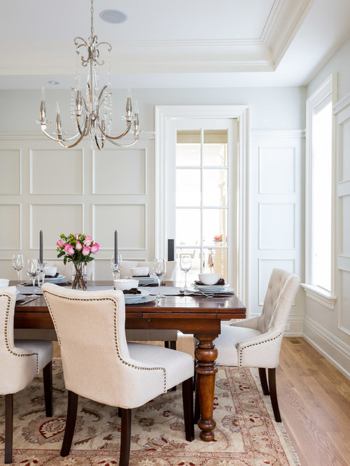 example of a classic medium tone wood floor dining room design in toronto with white walls