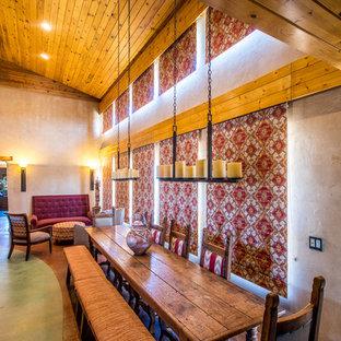 Foto de comedor de cocina de estilo americano, de tamaño medio, con paredes beige, suelo de cemento, estufa de leña, marco de chimenea de hormigón y suelo verde