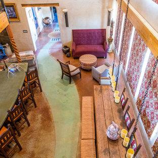 Foto di una sala da pranzo aperta verso la cucina stile americano di medie dimensioni con pareti beige, pavimento in cemento, stufa a legna, cornice del camino in cemento e pavimento verde