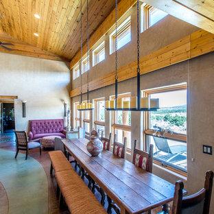 Modelo de comedor de cocina de estilo americano, de tamaño medio, con paredes beige, suelo de cemento, estufa de leña, marco de chimenea de hormigón y suelo verde