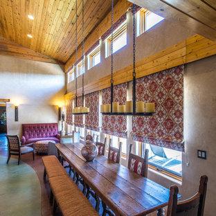 Diseño de comedor de cocina de estilo americano, de tamaño medio, con paredes beige, suelo de cemento, estufa de leña, marco de chimenea de hormigón y suelo verde