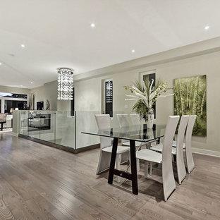 Foto di una sala da pranzo aperta verso il soggiorno contemporanea di medie dimensioni con pareti beige, pavimento in laminato, nessun camino e pavimento marrone