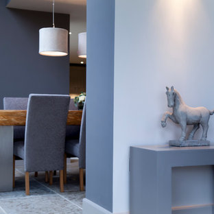 Large contemporary dining room in Cheshire with white walls and limestone flooring.