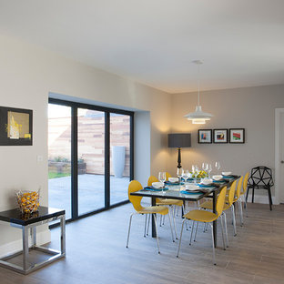 Photo of a retro enclosed dining room in West Midlands with grey walls and medium hardwood flooring.